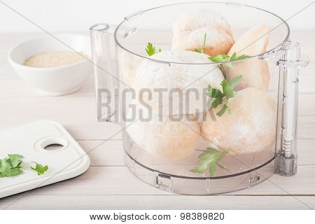 stale rolls with fresh parsley in food processor prepared to be ground into breadcrumbs