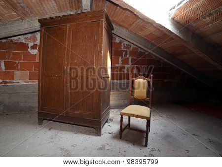 Wooden Wardrobe And An Antique Chair In The Dusty Attic