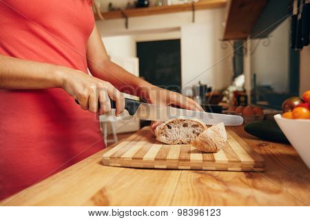 Woman slicing loaf of bread on cutting board with kitchen knife. Close-up shot of female hands cutting bread on kitchen counter focus on bread. poster