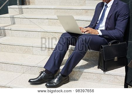 Contemporary businessman typing on laptop keypad while sitting on stairs outdoors
