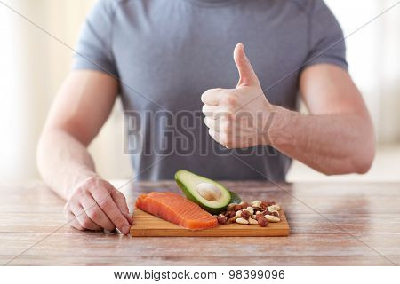healthy eating, diet, gesture and people concept - close up of male hands showing thumbs up with food rich in protein on cutting board on table