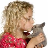 young girl holding and kissing a little gray rabbit poster