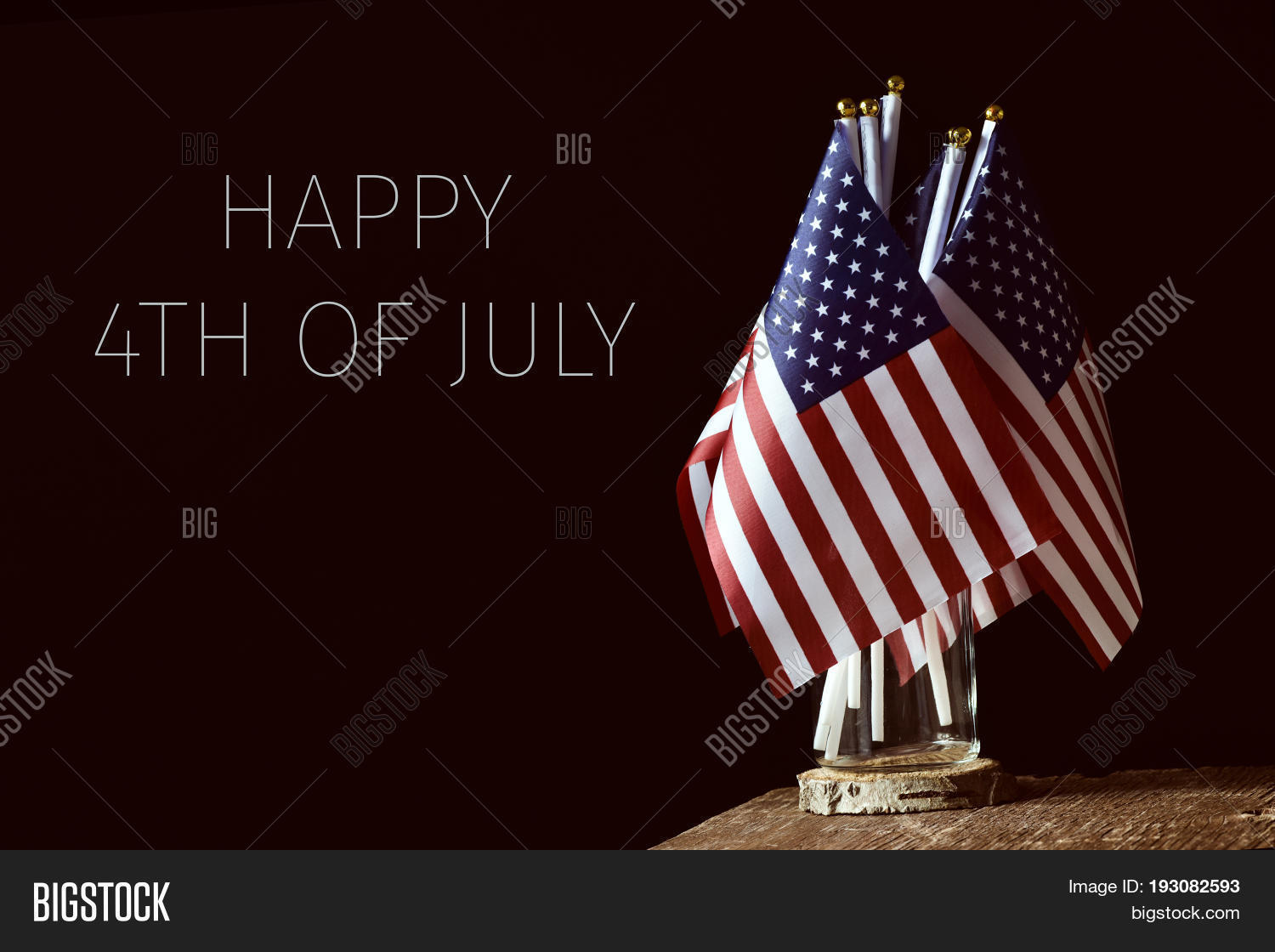 Some American Flags In A Glass Jar On Rustic Wooden Surface And The Text