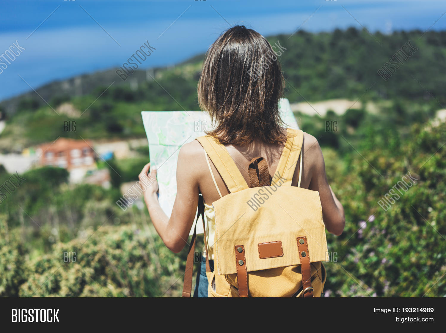 838f27ae22ee Hipster young girl with bright backpack looking at a map and poining hand  the travel plan