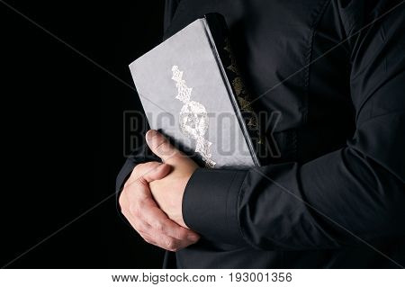 Man's hands holds Koran/ Quran - holy book of muslims isolated on black background with copy space.
