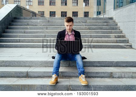 Stylish young man in jacket and jeans sitting on the stairs and typing on laptop computer outdoors. Technology and communication concept
