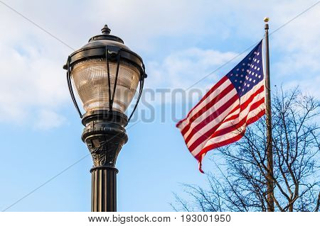 A streetlight and the flag of USA on the background of cloudy sky