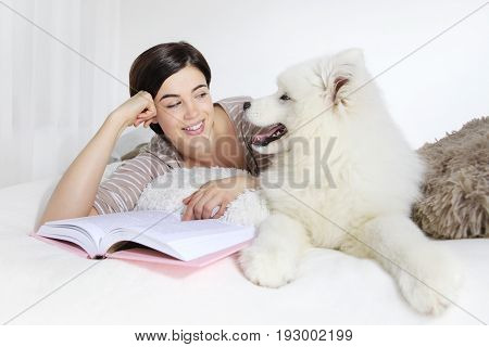 smiling woman with pet dog and book