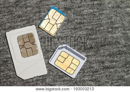 Set of mini micro and nano simcard. Isolated on grey cloth texture background
