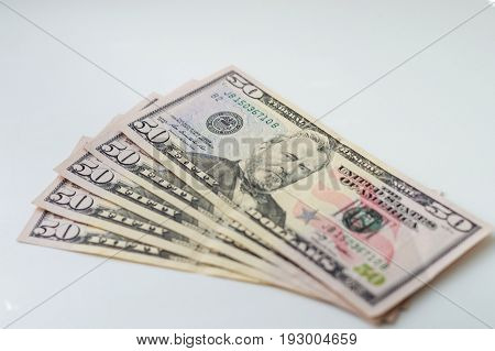 A Stack Of Fifty Dollar Bills Fanned Out On A White Background