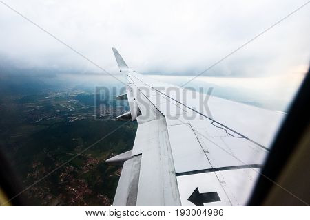 Looking trough window of an aircraft airplane or plane wing. View from plane window during landing or takeoff over the city urban area.