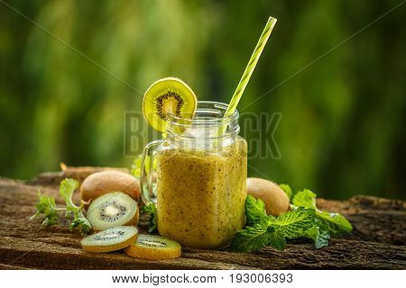 Healthy green smoothie made of kiwi, outdoor shot
