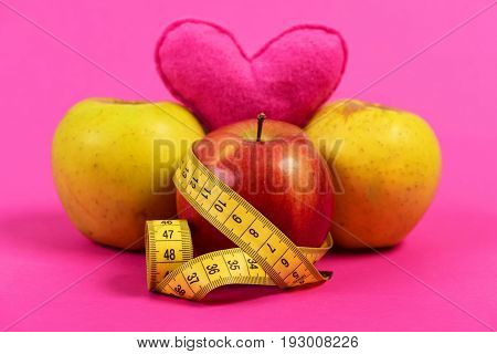 Concept of useful nutrition fitness lifestyle and vitamins: heart near fruit and tape measure isolated on pink background