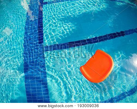 swimming board floating in the pool on sunny day