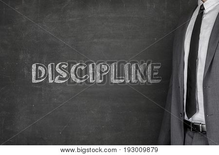 Midsection of businessman wearing suit while standing by discipline text on blackboard
