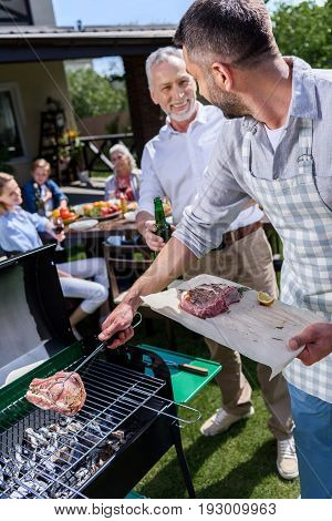 Adult father and son making barbecue and drinking beer while family sitting at table outdoors