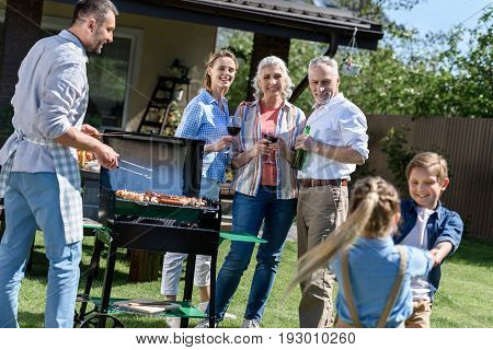Smiling Man Cooking Food On Barbecue With Family Enjoying Weekend Near By
