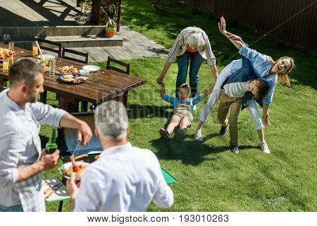 Cheerful Women Playing With Kids While Men Cooking Meat During Barbecue
