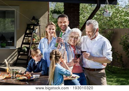 Portrait Of Smiling Multi-generational Family Having Picnic On Patio At Daytime