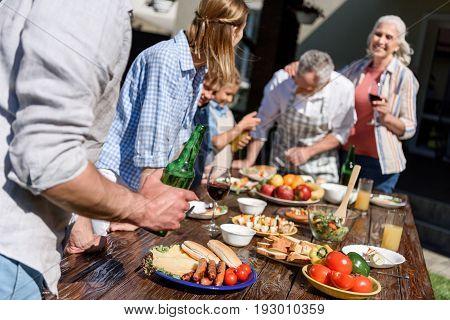 happy multi-generational family having picnic on patio at daytime