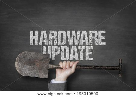 Cropped image of businessman's hand holding spade under hardware update text on blackboard