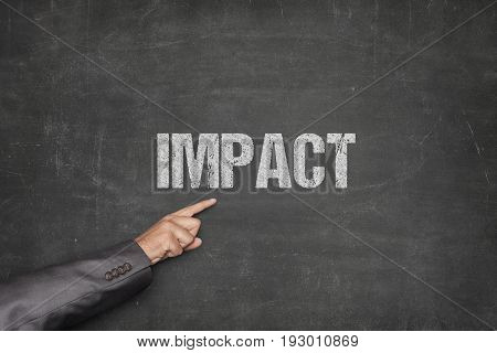 Cropped image of businessman pointing at impact text on blackboard