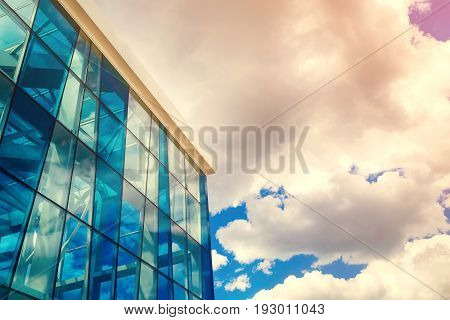 Bottom view of modern glass blue business centre architecture toned free space. Sunlight reflection on glass abstract building. Sky with clouds background. Windowed corner of office building