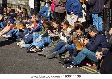 LONDON , APRIL 23 2017: Unidentified A group of people eat a sandwich sitting down the street. During lunch break this is the fastest way to have lunch