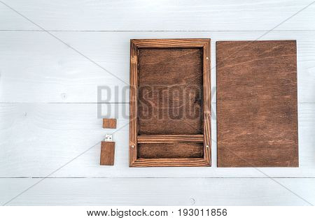 Empty wooden box for gift or photo with usb stick free space. Packaging for photo and USB drives on white wooden background. Information and mail concept