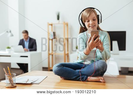 Own little world. Savvy smart cheerful girl using her phone for choosing the right song while wearing headphones and sitting in dads office