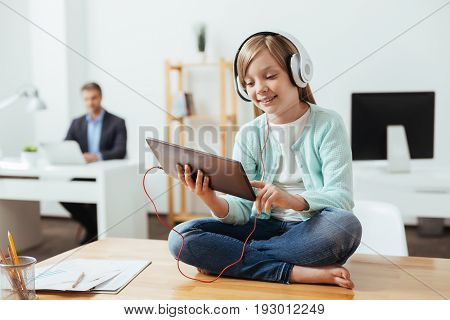 Portable entertainment. Sociable lively diligent child using her gadget while wearing headphones and sitting on the table in dads office