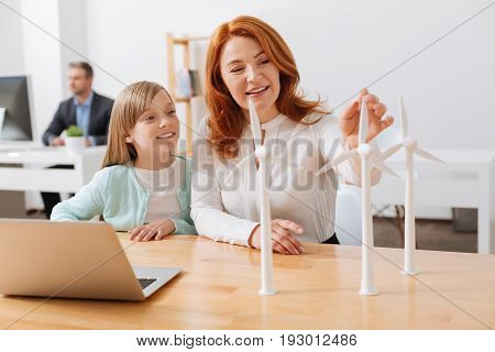 Wind force. Talented ambitious gorgeous woman working for engineering company and showing her child their new project while explaining how wind turbines working