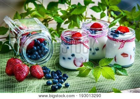 Three Jars Of Yogurt With Blueberries And Strawberries, Square.