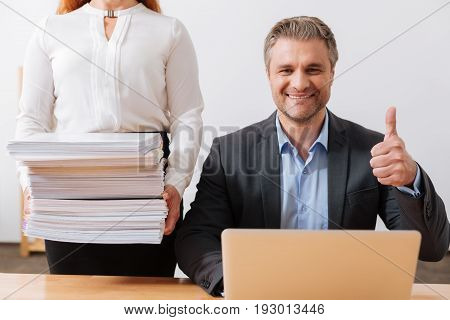 Productive employee. Analytical charming lively employee sitting in the office and having a productive day while working with loads of papers