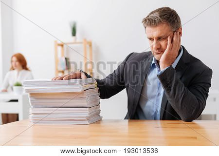 How can I handle all of this. Emotional weary hardworking man sitting at his workplace and looking at the amount of work he needing completing today