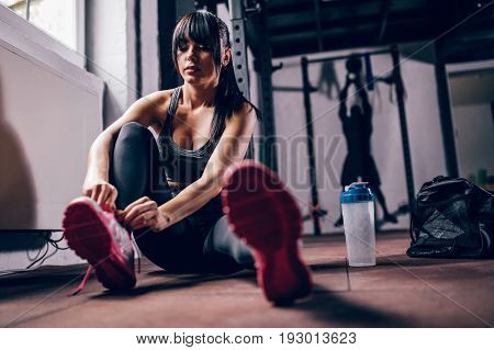 Woman tying her shoes and getting ready for training in the gym.