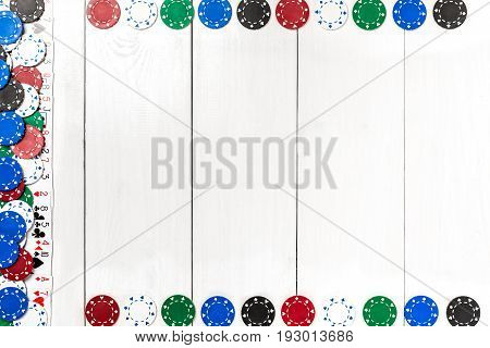 Playing cards and poker chips on white wooden background. Top view. Copyspace. Poker.