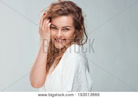 Sensual Smiling Woman In White Robe Touching Her Face, Isolated On Grey