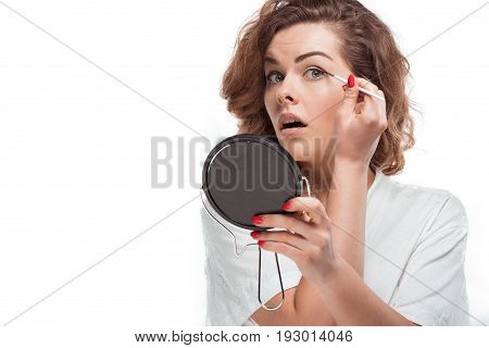 Portrait Of Woman With Mirror In Hand Putting Eyeliner Isolated On White