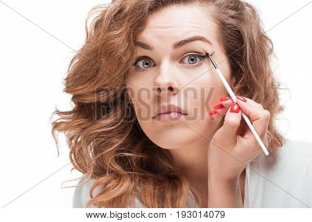 Focused Woman Looking At Camera While Putting Eyeliner Isolated On White