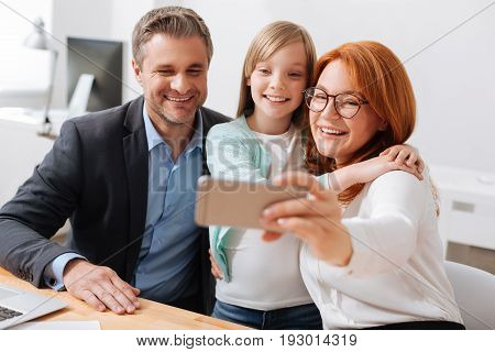 Family business. Sincere lively bright child and her parents remembering nice day they spending together while taking their child to work with them