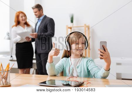 Like a professional. Sociable enthusiastic pretty girl using her smartphone for making a picture and sharing it with her friends online