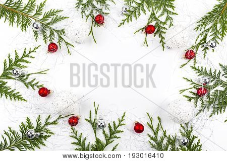 Wide arch shaped Christmas border on white background composed of fresh fir branches and ornaments red and silver balls with bear and boot