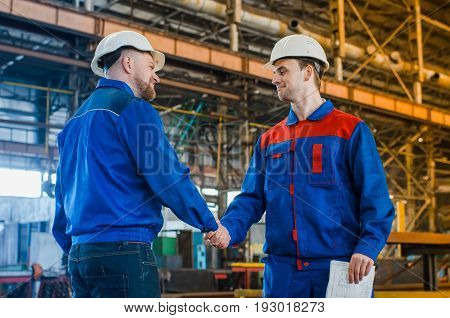Handshake of two men of engineers in white helmets and protective overalls against the background of a metallurgical plant. Completion of the transaction. conclusion of a contract. Conclusion of a contract