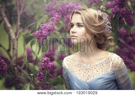 Portrait of a beautiful young blond woman in lilac bushes, admiring flowers. Girl in blue dress.