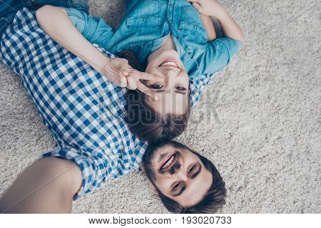 Smile! Upside Down Shot Of A Couple Of Teens. Young Siblings Are Lying At Home On The Carpet And Tak