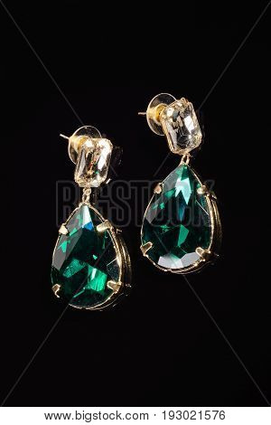 two earrings with green stones on the black
