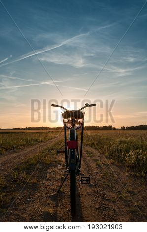 Bike at sunset, Blue sky with clouds and green field along a rural road, Bicycle on the bandwagon