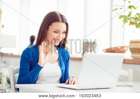 Hello There! Young Cheerful Lady Is Waving To The Camera While Having Video Call In Light Modern Des