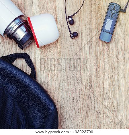 Different objects on wooden background: backpack thermos earphones music player